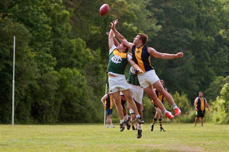 Os jogadores saltam para a bola no jogo de futebol das regras do australiano fotografia de stock royalty free