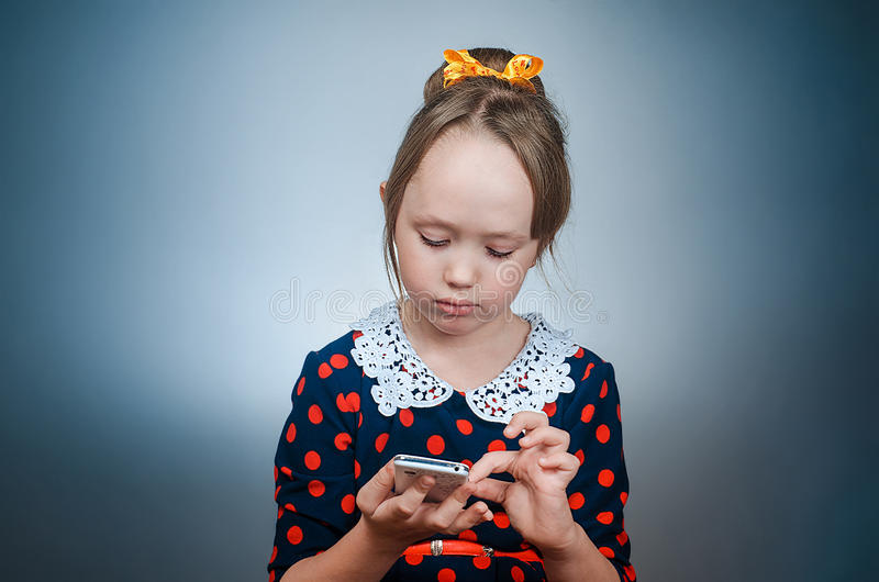 Os jogos da menina com telefone branco imagens de stock