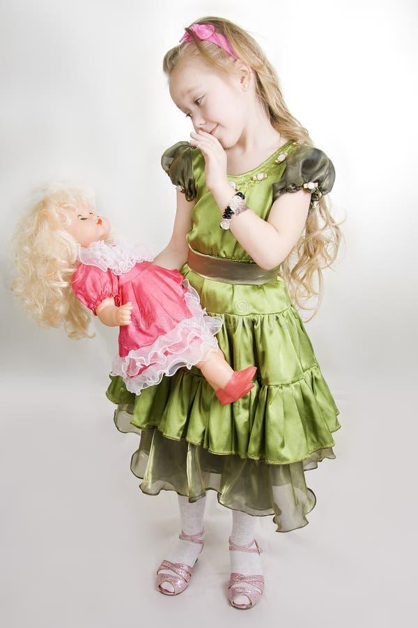 Os jogos da menina com uma boneca foto de stock royalty free