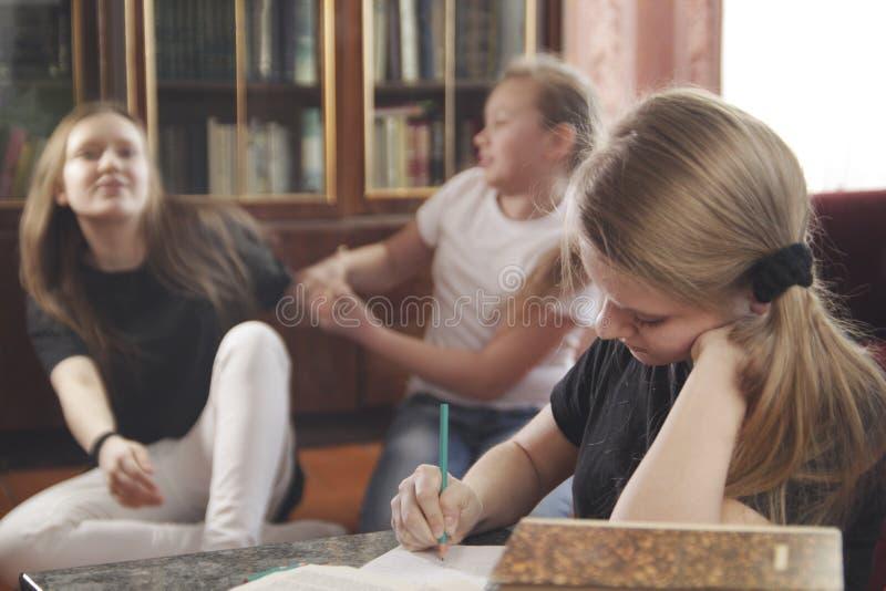 Os jogos dos adolescentes das meninas e impedem para fazer lições imagem de stock royalty free