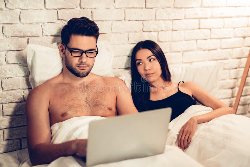 Os jovens acoplam-se na cama, esposa furada portátil de trabalho do homem imagem de stock royalty free