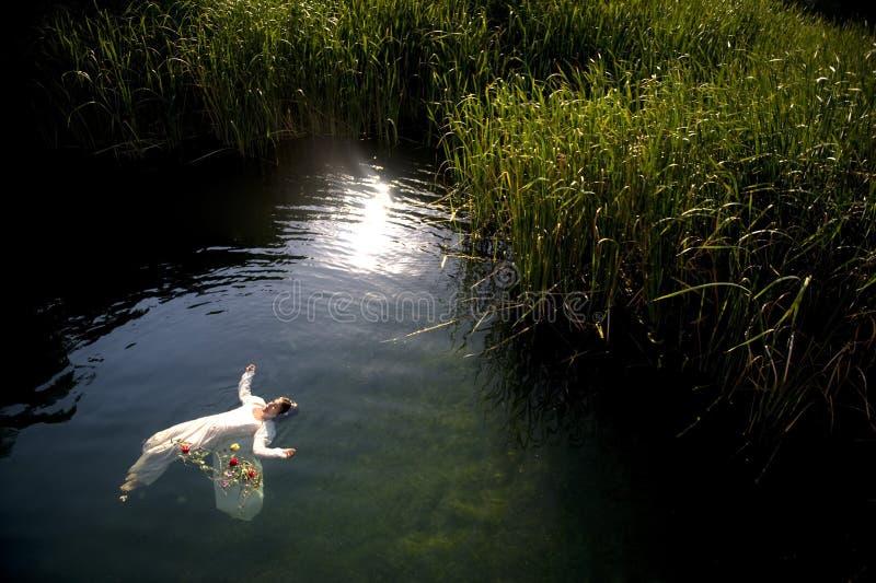 Os jovens afogam a mulher no lago fotografia de stock
