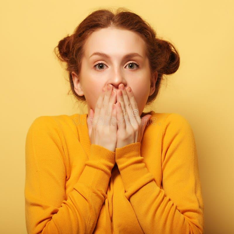 Os jovens bonitos surpreenderam a mulher do redhair sobre o fundo amarelo imagem de stock royalty free
