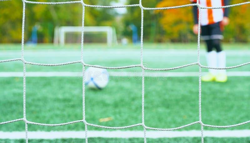 Os jovens borraram o jogador de futebol que toma um pontapé de grande penalidade contra a rede do objetivo imagem de stock royalty free