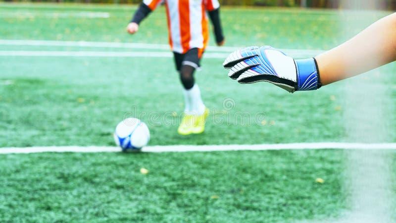 Os jovens borraram o jogador de futebol que toma um pontapé de grande penalidade contra a rede do objetivo imagem de stock