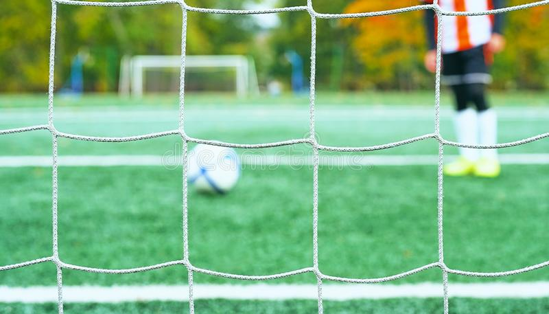 Os jovens borraram o jogador de futebol que toma um pontapé de grande penalidade contra a rede do objetivo fotografia de stock