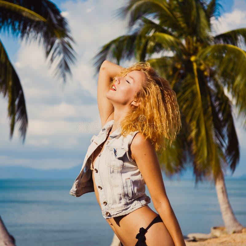 Os jovens bronzeam-se a menina 'sexy' magro do ruivo no fundo do céu azul no mar do verão imagem de stock royalty free