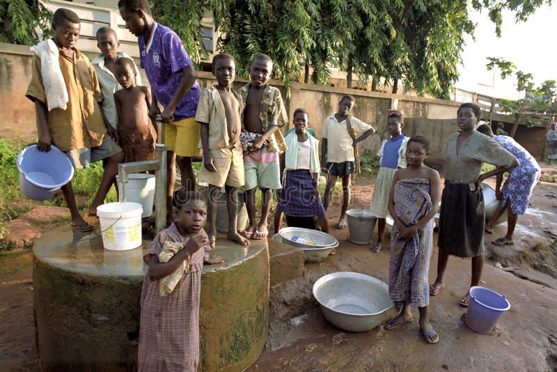 Os jovens buscam a água em uma bomba de água fotografia de stock royalty free