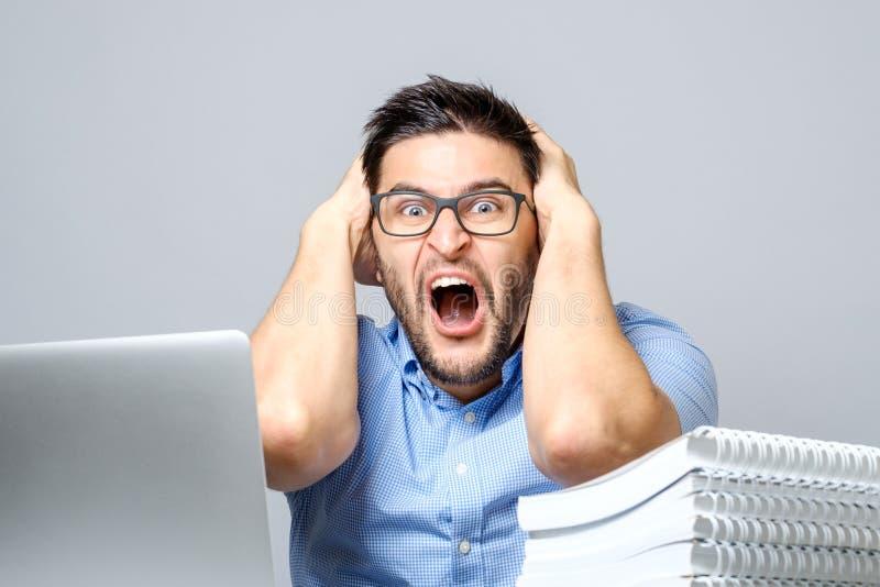 Os jovens chocaram o homem na camisa azul usando o portátil imagens de stock