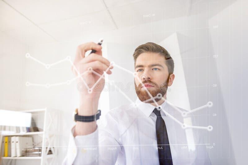 Os jovens concentraram a carta do desenho do homem de negócio na tela virtual foto de stock