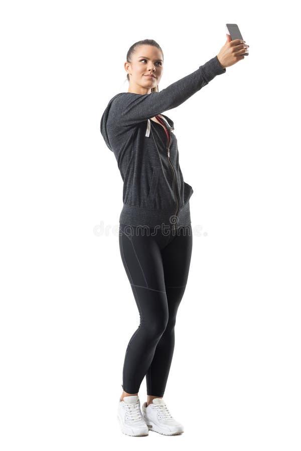 Os jovens couberam a mulher desportiva que toma a imagem com o smartphone fotografia de stock royalty free