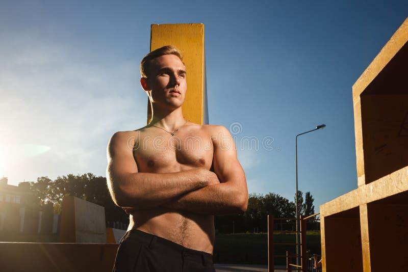 Os jovens couberam o homem descamisado que exercita na terra de esportes exteriores foto de stock royalty free