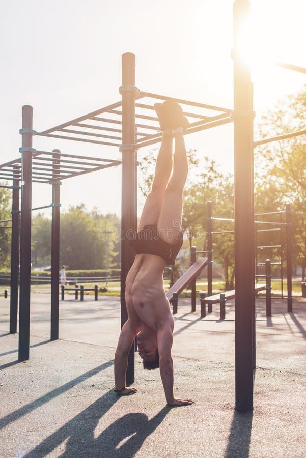 Os jovens couberam o homem muscular que faz o exercício do pino fora fotografia de stock royalty free