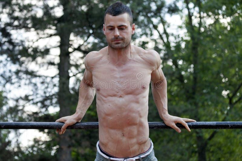 Os jovens couberam o homem muscular que faz exercícios na barra horizontal imagem de stock