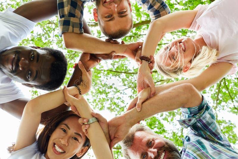 Os jovens cruzam as mãos para a solidariedade imagem de stock royalty free