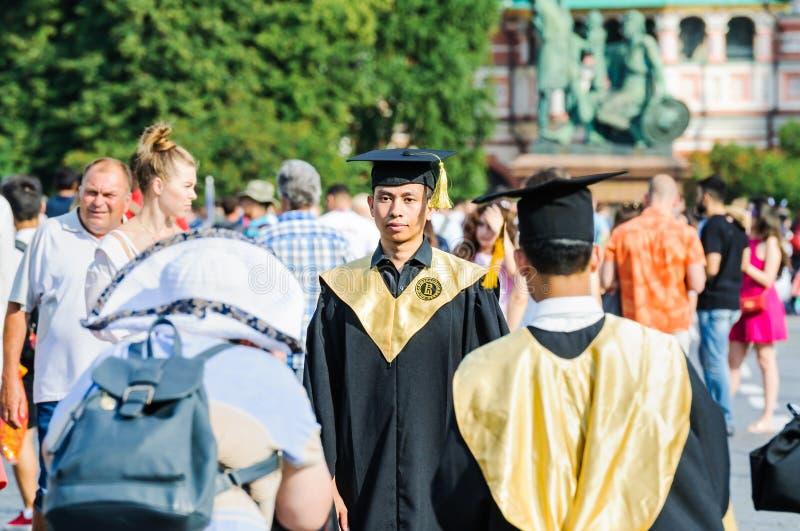Os jovens da aparência asiática nos envoltórios de graduados da universidade fotografaram no quadrado vermelho imagem de stock