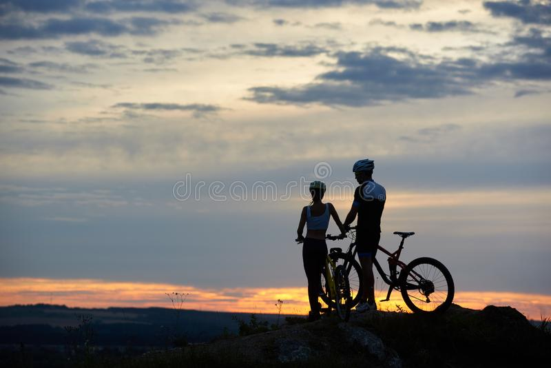 Os jovens de vista traseira dois com Mountain bike estão sobre o penhasco com cenário bonito no por do sol fotografia de stock