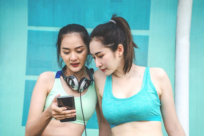 Os jovens dois amigos das mulheres dos esportes na roupa dos esportes estão sentando-se no banco, relaxam após o treinamento dos  imagens de stock royalty free