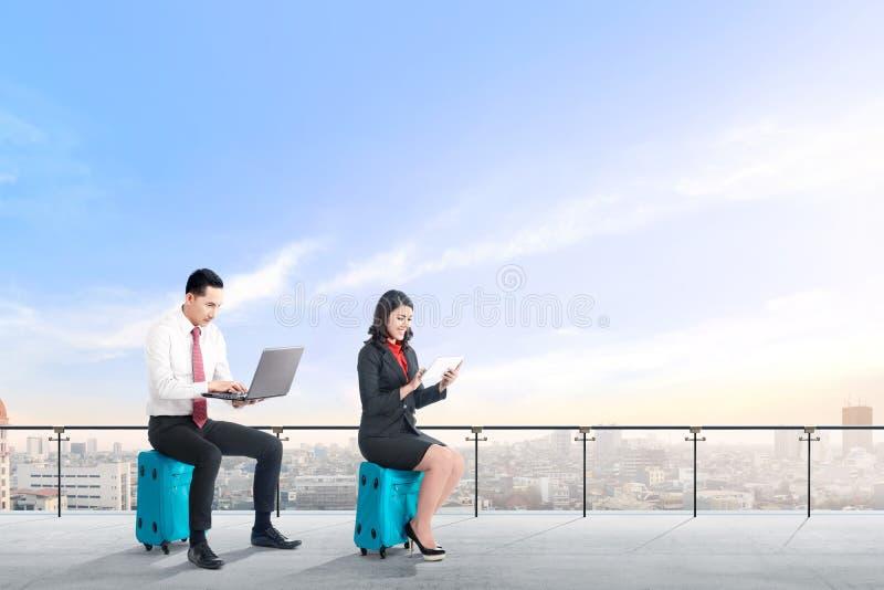 Os jovens dois executivos asiáticos que sentam-se na mala de viagem azul mantêm o portátil e a tabuleta que trabalham no terraço  fotos de stock