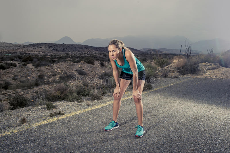 Os jovens esgotaram a mulher do esporte que corre fora na estrada asfaltada que respira foto de stock