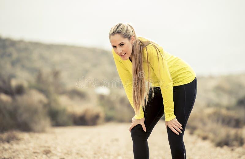 Os jovens esgotaram a mulher do esporte que corre fora na estrada suja que respira foto de stock royalty free