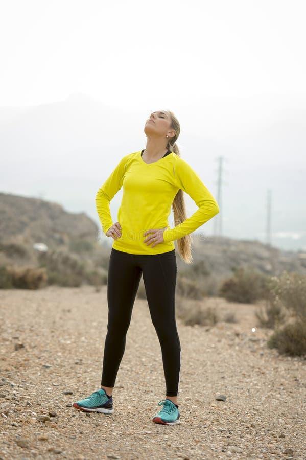 Os jovens esgotaram a mulher do esporte que corre fora na estrada suja que respira fotos de stock royalty free