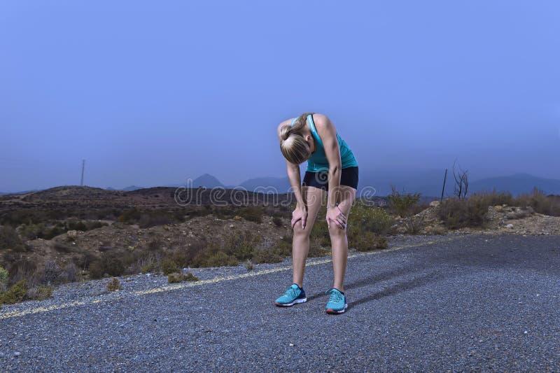 Os jovens esgotaram a mulher do esporte que corre fora na parada da estrada asfaltada para respirar e ter um resto após o esforço imagens de stock royalty free