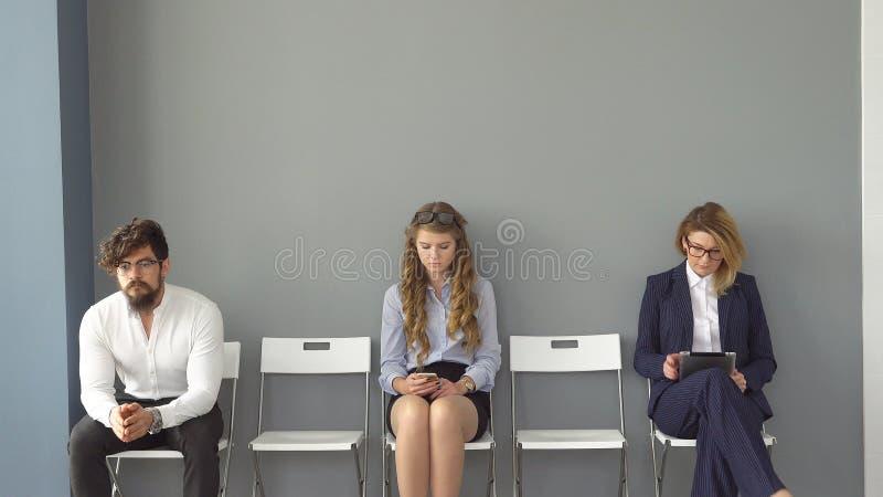 Os jovens esperam as entrevistas que sentam-se em cadeiras em um prédio de escritórios a entrevista para o trabalho os recrutas s fotografia de stock