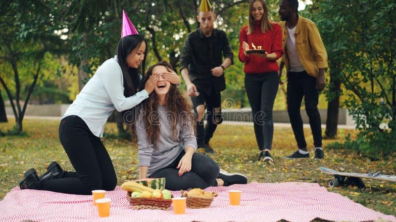 Os jovens estão felicitando a menina no aniversário que traz o bolo que ri e que exulta durante o partido exterior no parque imagem de stock