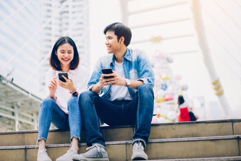 Os jovens est?o usando o smartphone e est?o sorrindo ao sentar-se no tempo livre Conceito da tecnologia fotografia de stock royalty free