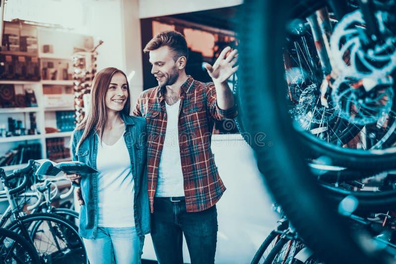 Os jovens felizes acoplam a conversa sobre a roda na loja da bicicleta imagens de stock