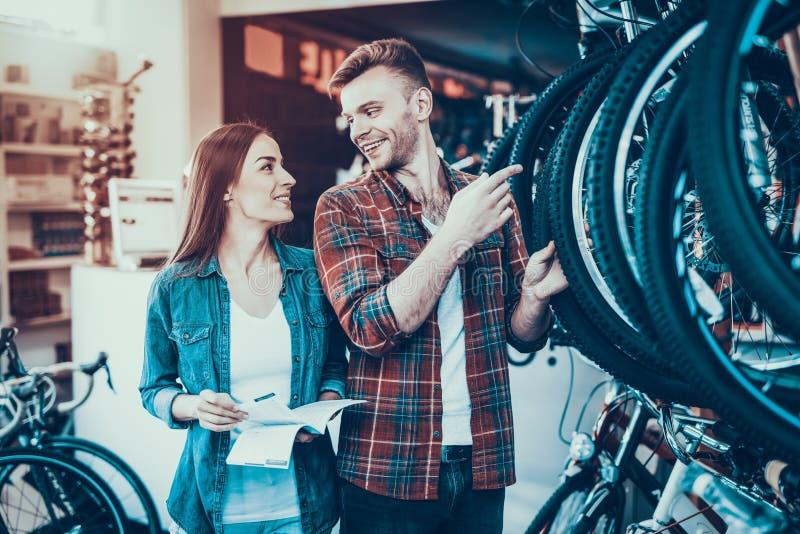 Os jovens felizes acoplam a conversa sobre a roda na loja da bicicleta fotografia de stock royalty free