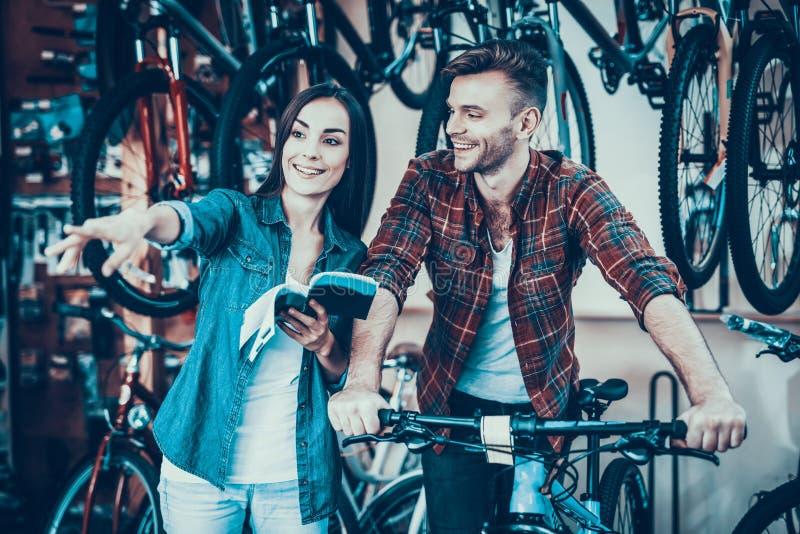 Os jovens felizes acoplam a fala quando escolha a bicicleta nova imagens de stock