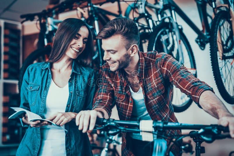 Os jovens felizes acoplam a fala quando escolha a bicicleta nova fotos de stock