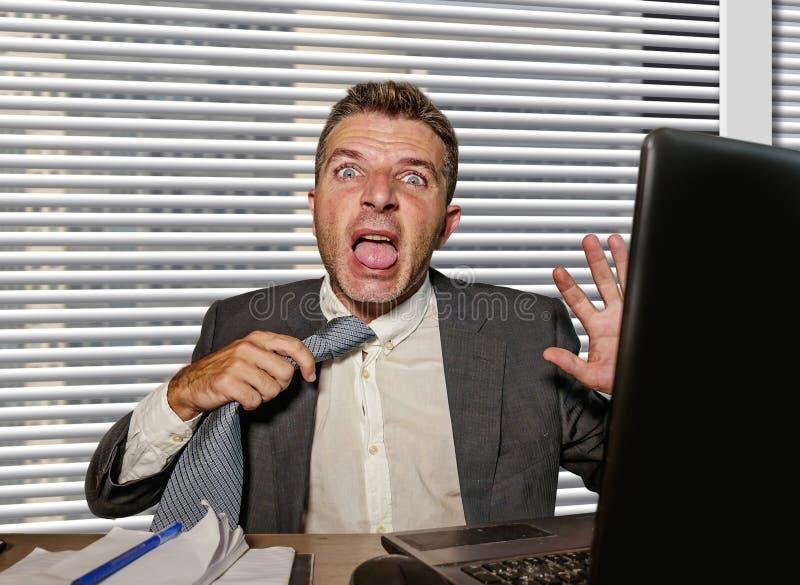 Os jovens forçaram e oprimiram o homem de negócios no terno que puxa seu funcionamento desesperado do laço na mesa do laptop do e fotos de stock