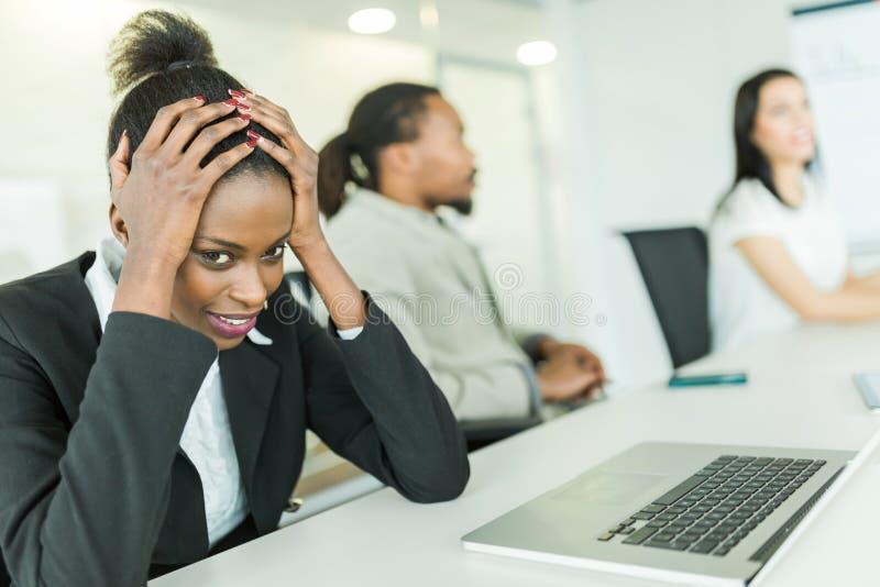 Os jovens forçaram a mulher de negócios que luta com uma dor de cabeça durante um b imagens de stock royalty free