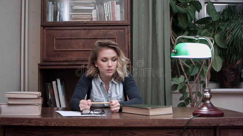 Os jovens forçaram o desperatley da mulher que olha livros e que joga um lápis na raiva fotografia de stock royalty free