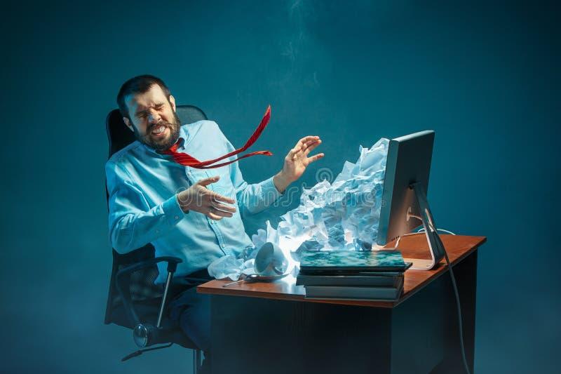Os jovens forçaram o homem de negócios considerável que trabalha na mesa na gritaria moderna do escritório na tela do portátil e  imagens de stock royalty free