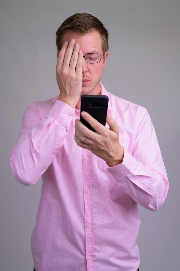 Os jovens forçaram o homem de negócios que usa o telefone e cobrindo a cara imagem de stock