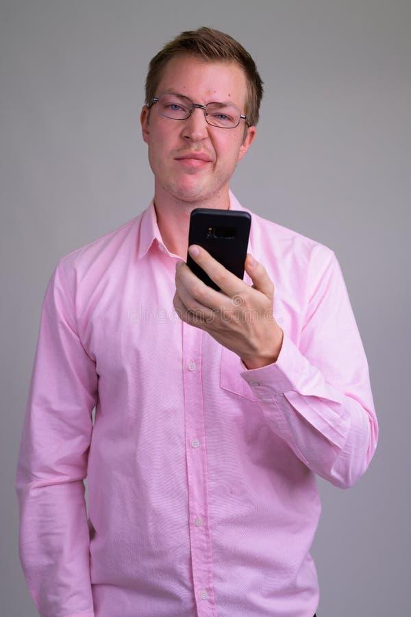 Os jovens forçaram o homem de negócios que usa o telefone e olhando frustrados fotografia de stock