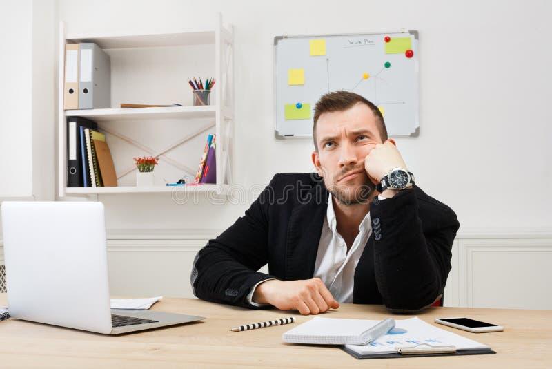 Os jovens furaram o homem de negócios com o portátil no escritório branco moderno fotografia de stock
