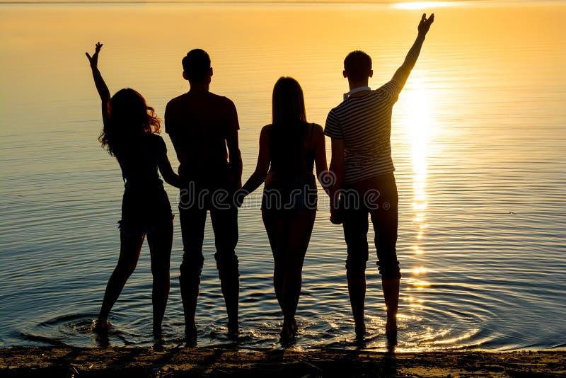 Os jovens, os indivíduos e as meninas, estudantes estão estando na praia fotografia de stock