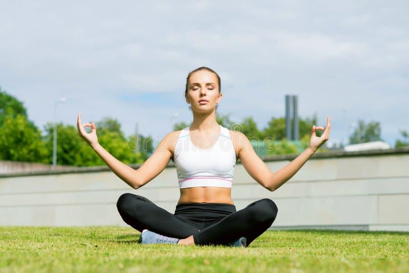 Os jovens, o ajuste e a mulher desportiva fazendo a ioga exercitam a meditação no parque Estilo de vida da aptidão, do esporte, o foto de stock