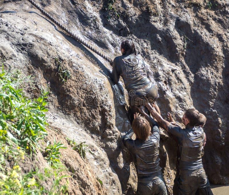Os jovens passam o curso de obstáculo Corredores de raça da lama Escalando a corda teamwork fotos de stock