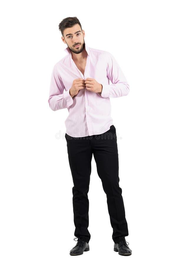 Os jovens preparam a abotoadura de sua camisa cor-de-rosa que olha a câmera fotografia de stock