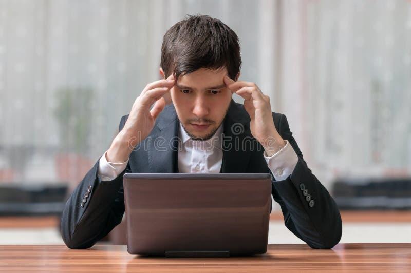 Os jovens pretendem e homem de negócios de pensamento que trabalha com portátil imagens de stock royalty free