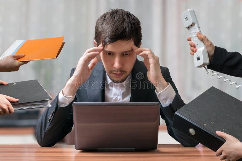Os jovens pretendem e o homem de negócios ocupado de pensamento está trabalhando com computador imagens de stock