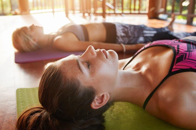 Os jovens que relaxam no savasana levantam na classe da ioga fotos de stock royalty free