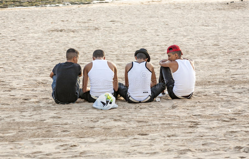 Os jovens que vestem os tanques de Bro sentam-se na praia foto de stock royalty free