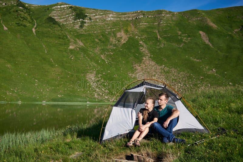 Os jovens sentam-se na barraca perto do lago contra o contexto da montanha verde fotos de stock